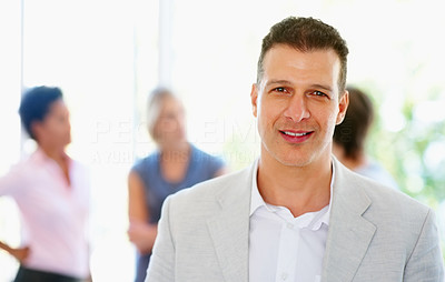 Buy stock photo View of man smiling with colleagues in background