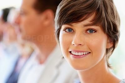 Buy stock photo Focus on attractive woman with team in row in background