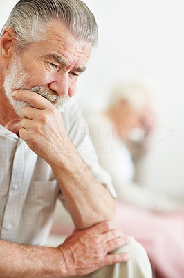 Buy stock photo Closeup shot of a unhappy senior man with his wife in the background