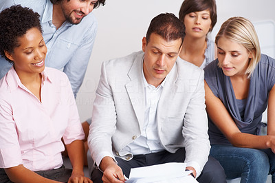 Buy stock photo Handsome business man showing document to his team