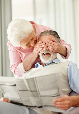 Buy stock photo Shot of a senior woman covering her laughing husband's eyes from behind