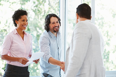 Buy stock photo Two male executives shaking hands while woman smiling