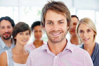 Buy stock photo Smiling young business man with his colleagues in background