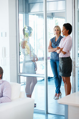 Buy stock photo Three business women standing and talking in office corridor