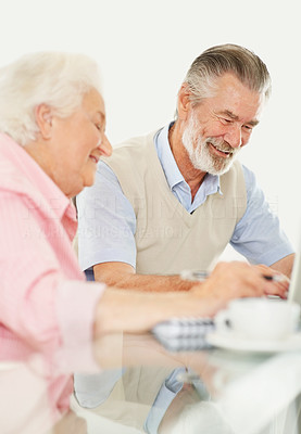 Buy stock photo Shot of a happy elderly couple working together on a laptop