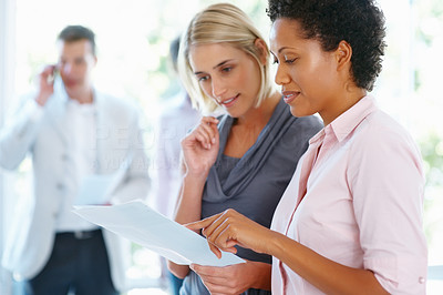 Buy stock photo Two business women reviewing documents with team in background