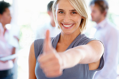 Buy stock photo Cheerful young woman giving thumbs up with colleagues in background