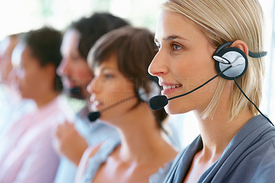 Buy stock photo Beautiful woman wearing headset with colleagues in background