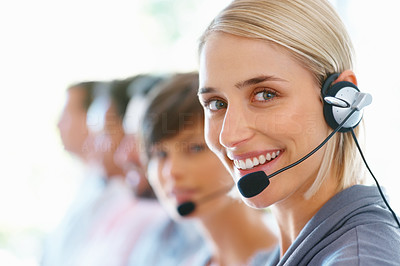 Buy stock photo Beautiful female executive wearing headset with colleagues in background