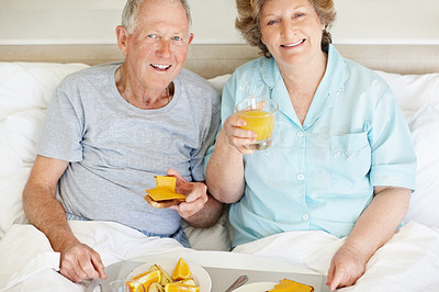Buy stock photo Portrait of a happy senior couple having breakfast sin bed