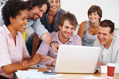 Buy stock photo Young business man points at laptop screen while discussing with team