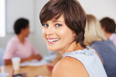 Buy stock photo Happy woman smiling with blur team in background