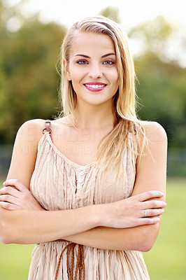 Portrait of a smiling, beautiful blonde woman standing in a field with her arms crossed
