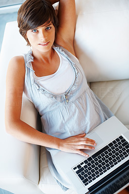 Buy stock photo Pretty young woman working on laptop from home