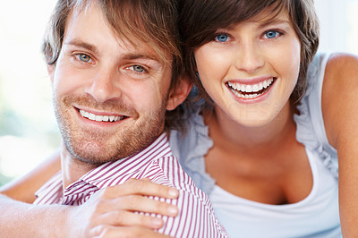 Buy stock photo Attractive young couple smiling while embracing