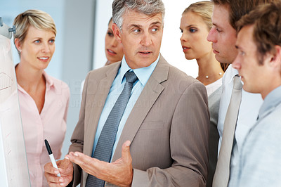 Buy stock photo Confident senior business man giving a presentation to his colleagues at office