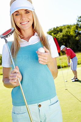 Smiling golfer with her putter and ball