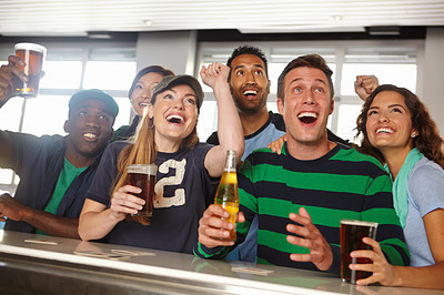 A group of friends cheering on their favourite team at the bar