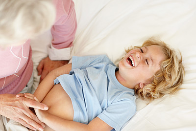 Buy stock photo Portrait of a mature woman tickling her grandson while lying in bed