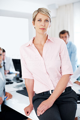 Buy stock photo Relaxed business woman standing in front of conference table with colleagues in background