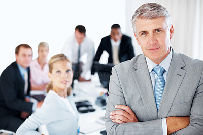 Buy stock photo Portrait of a successful young businessman with his hands folded and his team working behind at office