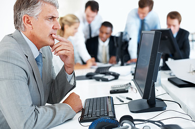 Buy stock photo Portrait of a successful mature businessman working on computer with his team at office
