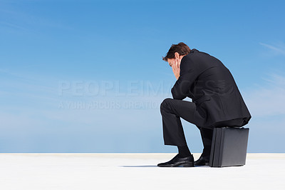 Depressed business man sitting on briefcase with copyspace