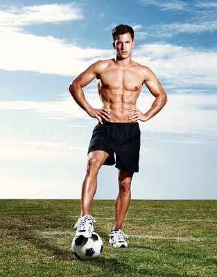 Confident male soccer player with a football