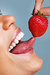 Detail shot of a seductive female licking a fresh strawberry