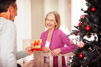 Mature man giving gift to cheerful wife on Christmas festival