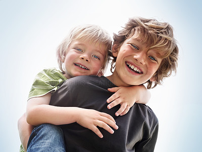 Cheerful young boy giving a piggyback ride to his brother