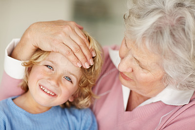 Buy stock photo Portrait of a grandmother feeling the forehead of a happy boy