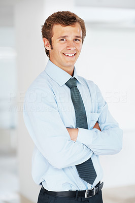 Buy stock photo Portrait of a smiling young businessman standing with his hands folded in office