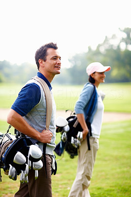 Man and woman carrying golf bags