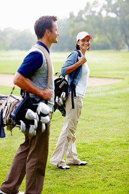 Couple walking on golf course with golf bags