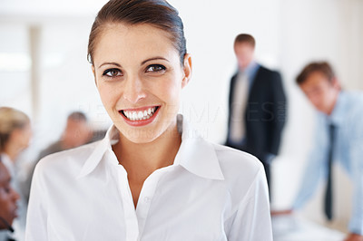 Buy stock photo Portrait of a happy young businesswoman with her colleagues working behind at office