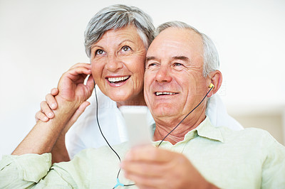 Smiling mature man and woman listening music
