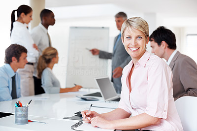 Buy stock photo Portrait of a smiling young business executive in a presentation with colleagues in background