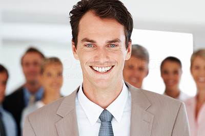 Buy stock photo Portrait of a smart young businessman leading a team in an office smiling