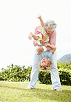 Mature woman holding her grandson upside down in park
