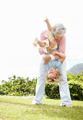 Buy stock photo Full length of a grandmother holding her grandson upside down in park