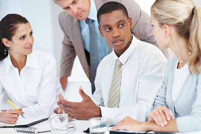Buy stock photo American african businessman explaining a project to colleagues at the office