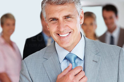 Buy stock photo Portrait of a successful senior businessman standing with colleagues in background