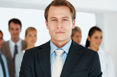 Buy stock photo Portrait of a smart  young businessman looking with an attitude and his colleagues behind at office