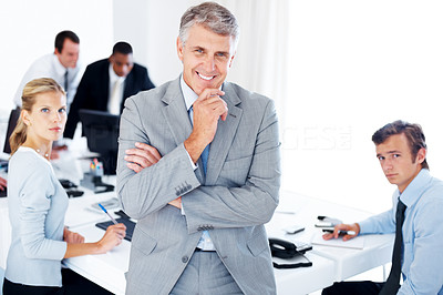 Buy stock photo Portrait of a happy senior businessman standing in office with staff working in background