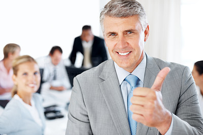 Buy stock photo Successful mature businessman gesturing thumbs up sign with colleagues woking in background