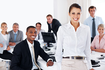 Buy stock photo Young smiling businesswoman at office with her colleagues sitting at a desk