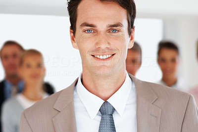 Buy stock photo Successful young businessman leading a team in an office smiling