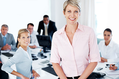 Buy stock photo Happy businesswoman standing in office with colleagues in back