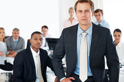Buy stock photo Confident young businessman standing in office with colleagues in back